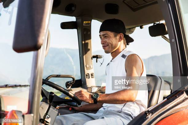 Portrait of Japanese farmer driving red tractor.