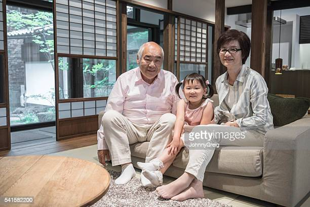 Portrait of Japanese grandparents with young girl at home