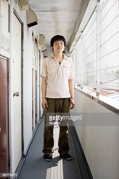 Portrait of Japanese man in front of his apartment