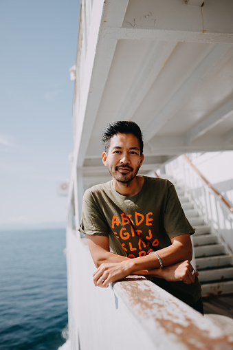 Portrait of Japanese man smiling at camera on ferry deck - gettyimageskorea
