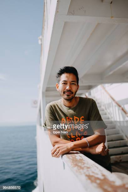 portrait of japanese man smiling at camera on ferry deck - passagerarbåt bildbanksfoton och bilder