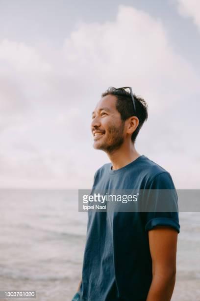 portrait of japanese man with sea at sunset - mid adult men ストックフォトと画像