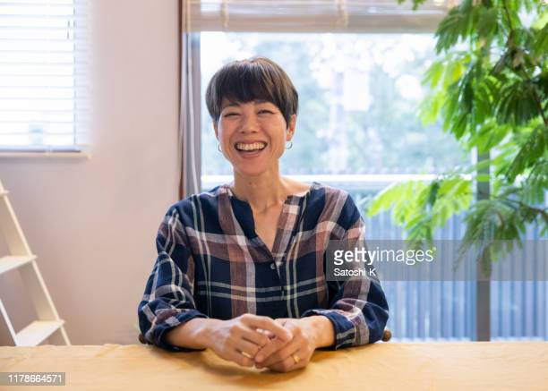 portrait of japanese mother sitting in dining room - mid adult stock pictures, royalty-free photos & images