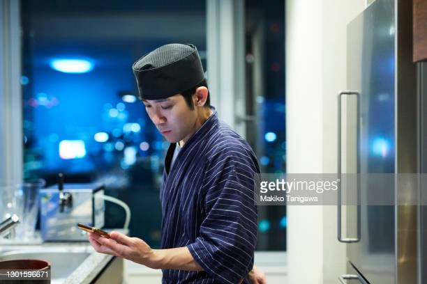 portrait of japanese sushi chef using smartphone - mid adult men stock pictures, royalty-free photos & images