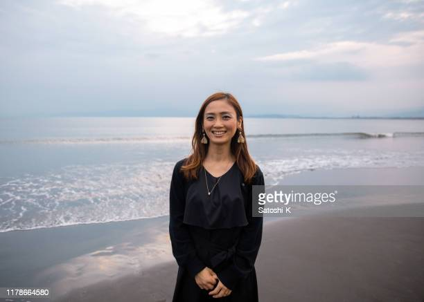 portrait of japanese woman standing on beach - kanagawa prefecture stock pictures, royalty-free photos & images