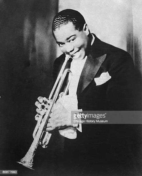 A portrait of jazz great Louis Armstrong smiling while holding his trumpet Chicago ca1920s
