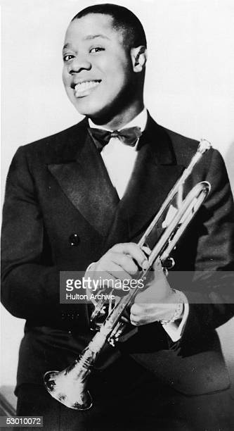 Portrait of jazz musician and actor Louis Armstrong posing with his trumpet, late 1920s.