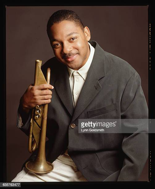 1990 Portrait of jazz musician Wynton Marsalis seated with an old style trumpet resting on his leg He is wearing black blazer with cream pants and...