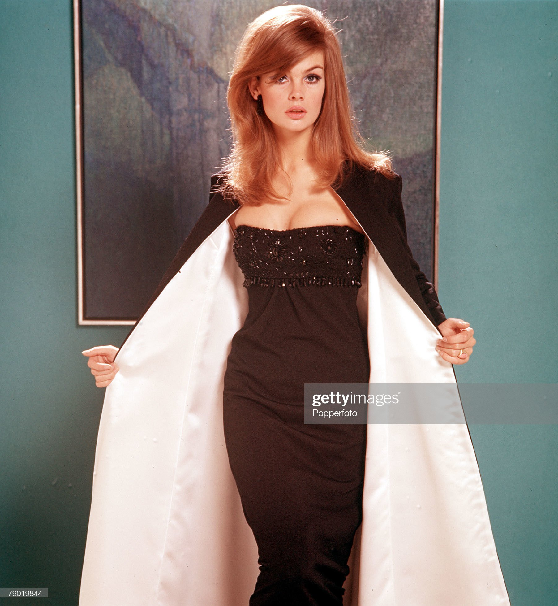 1965. A portrait of Jean Shrimpton wearing a black strap-less evening dress whilst holding open a smart white-lined long black jacket with a serious expression towards the camera. : News Photo
