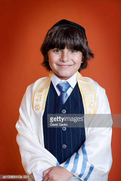 Portrait of jewish boy (4-5) wearing tallith and scull cup, smiling