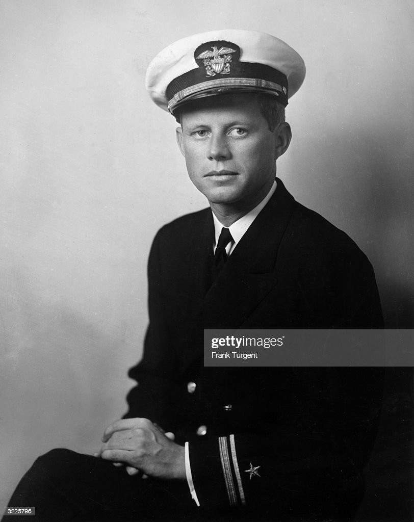 Portrait of John F Kennedy, future US senator and president, wearing his U.S. Navy uniform and posing with his hands in his lap, World War II (1939-1945), circa 1940. During the war, Kennedy served as a PT boat commander in the Pacific, earning medals for rescuing most of his crew after their boat was sunk in action.