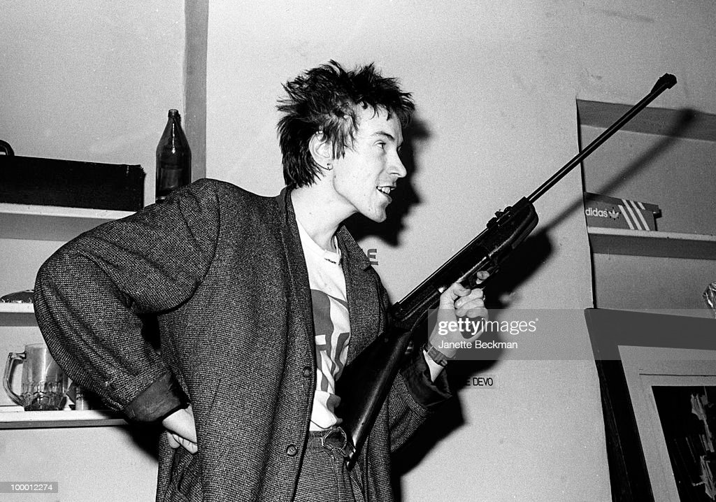 Portrait of John Lydon of the post-punk band Public Image Ltd as he poses with an air gun in his apartment, London, England, 1979.