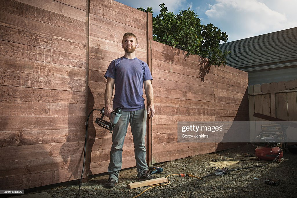 Portrait of joiner in backyard in front of new fence : Stock Photo