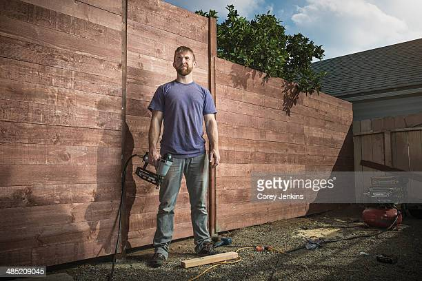 portrait of joiner in backyard in front of new fence - orgoglio foto e immagini stock