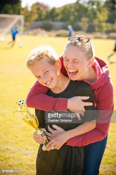 portrait of joyful mother, son after award ceremony - mama futbol fotografías e imágenes de stock