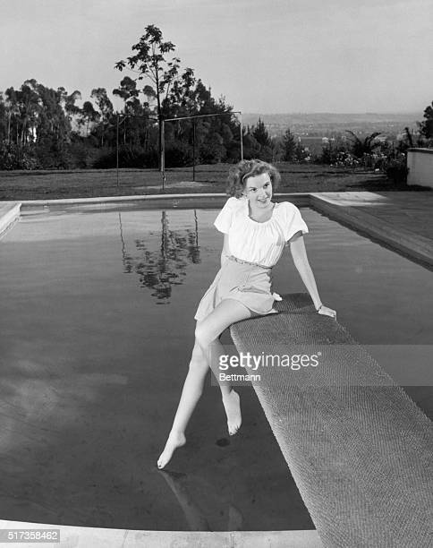 Portrait of Judy Garland dressed in a short skirt and blouse, seated on the diving board of an outdoor swimming pool. She is stretching her leg to...