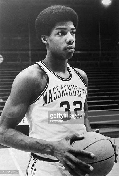 Portrait of Julius Erving, basketball player for University of Massachusetts, shown from the waist-up, in uniform, holding basketball.