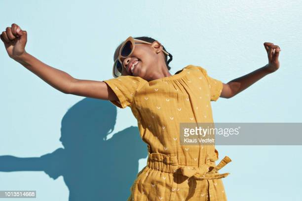 portrait of jumping cool girl with sunglasses - kindheit stock-fotos und bilder