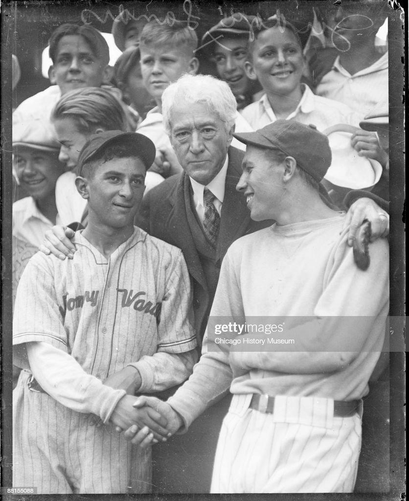 Portrait of Kenesaw Mountain Landis, Commissioner of Baseball from 1920-1944 and U.S. District Court Judge for the Northern District of Illinois, standing with two baseball players in an outdoor stadium in Chicago, Illinois, 1928. Landis is standing behind a low wall in the stands, and the two baseball players are standing and shaking hands on the field. Children are standing behind Landis. From the Chicago Daily News collection.