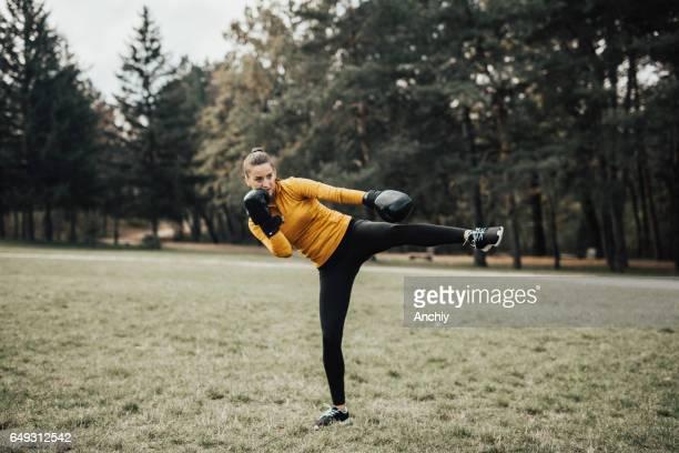 Portrait of kickboxing woman doing a kick