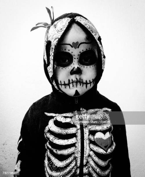portrait of kid with day of the dead make-up against wall - muro stock photos and pictures