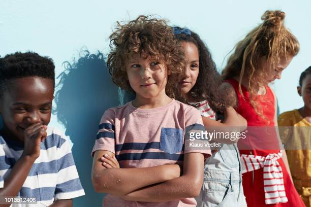 portrait of kids hanging out & playing together on blue backdrop in sunlight - cinco pessoas - fotografias e filmes do acervo