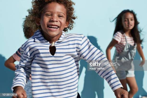 portrait of kids hanging out & playing together on blue backdrop in sunlight - 8 9 jahre stock-fotos und bilder
