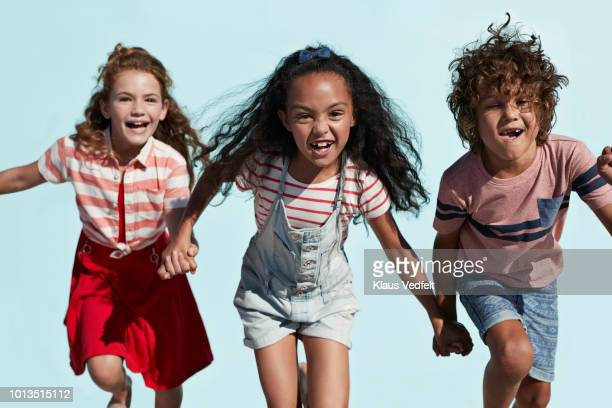 portrait of kids holding hands and running together, on blue backdrop in summer - children only stock pictures, royalty-free photos & images
