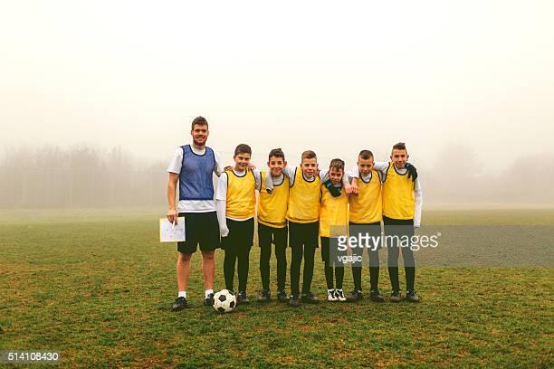 Retrato de los niños, el equipo de fútbol con el entrenador después de jugar