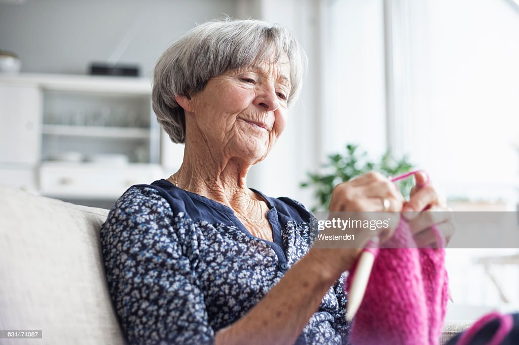 Portrait of knitting senior woman sitting on couch at home : Stock-Foto