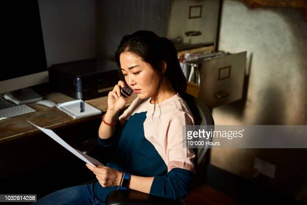 portrait of korean woman on cell phone reading important document - small business or entrepreneur stock photos and pictures