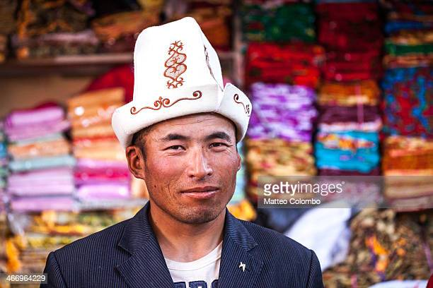 Portrait of kyrgyz ethnicity man with traditional hat, at the local bazaar of Kashgar with silk textiles in the background. Kashgar, Xinjiang...