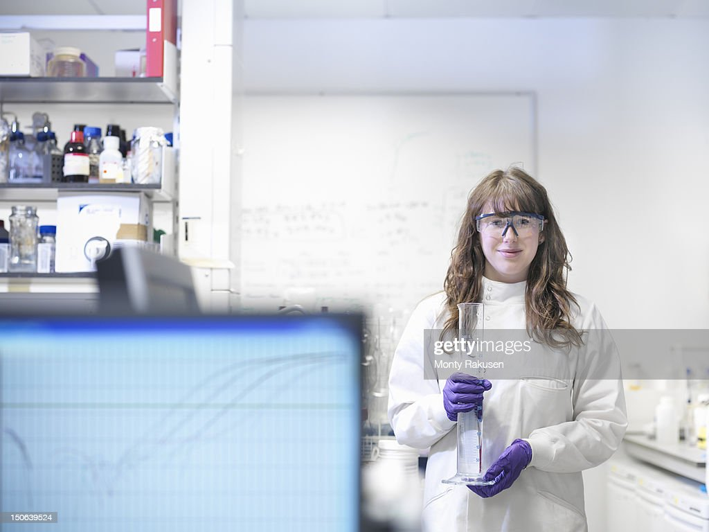 Portrait of laboratory technician holding measuring cylinder and working with genomic and protemcis : Foto de stock