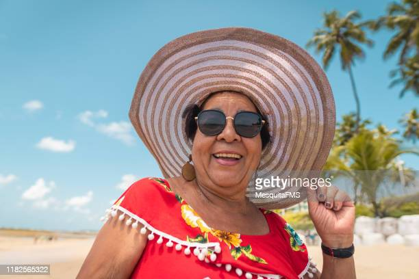 portrait of lady enjoying the tropical beach - multi colored hat stock pictures, royalty-free photos & images