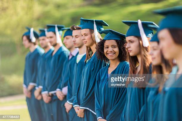 Portrait of large group of graduation students outdoors.