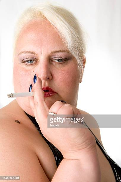 portrait of large scantily dressed woman smoking. - beautiful women smoking cigarettes stock photos and pictures