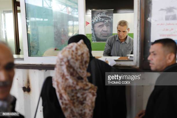 A portrait of late Palestinian leader Yasser Arafat above his national flag adorns a passport control station held by the Palestinian Authority at...