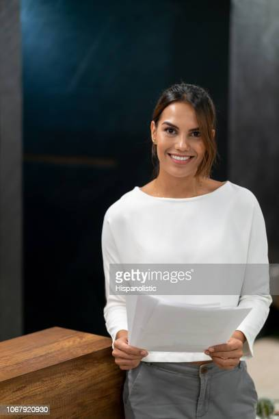 Portrait of latin american beautiful businesswoman at the office looking at camera smiling while holding documents