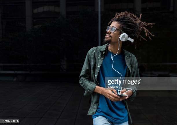 Portrait of latin american black man holding his smartphone and listening music smiling