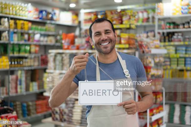 portrait of latin american business owner of a small market holding an open sign smiling at camera - retail occupation stock pictures, royalty-free photos & images