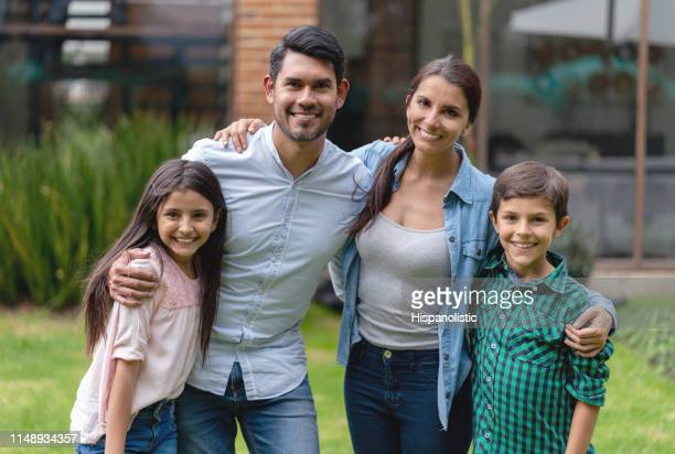 portrait of latin american family at their home backyard smiling at camera - hispanolistic stock photos and pictures