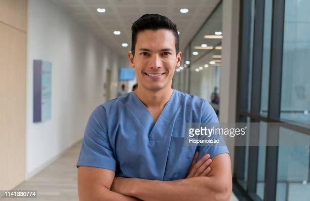 portrait of latin american male nurse at the hospital facing camera smiling with arms crossed - hispanolistic stock photos and pictures