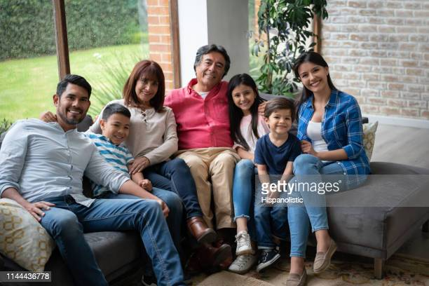 portrait of latin american multi generation family sitting on couch at home all looking at camera smiling - hispanolistic stock photos and pictures