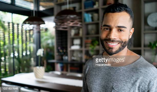 Portrait of latin american real estate agent looking at camera smiling while standing at a modern property