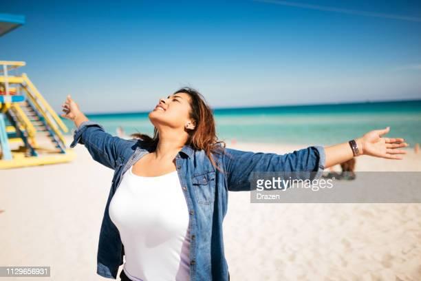 porträt von latina frau am strand in usa - kolumbianische frau lebt in florida, usa - dicke frauen am strand stock-fotos und bilder