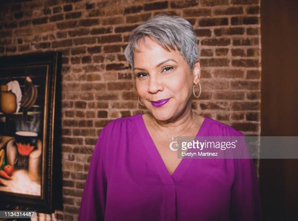 portrait of latina woman with short gray hair. exposed brick wall and painting in the background. - evelyn martinez stock pictures, royalty-free photos & images