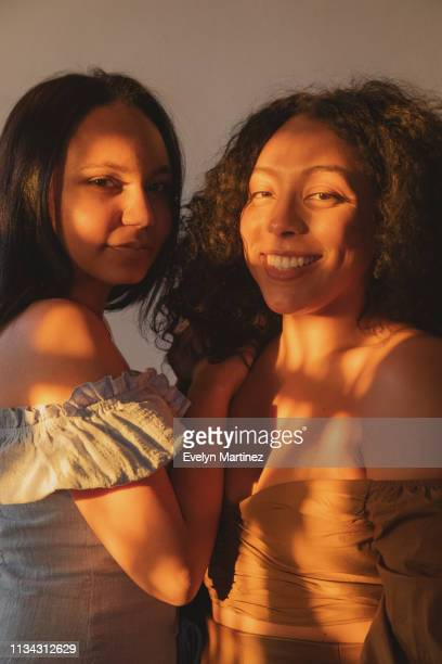 portrait of latina women in the sunlight. latina woman in the blue dress has her hand placed on her friend's shoulder. latina woman on the left is smiling, not showing teeth. latina woman on the right is smiling. - evelyn martinez stock pictures, royalty-free photos & images