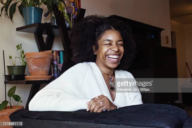 portrait of laughing african-american woman at home - showus stock pictures, royalty-free photos & images