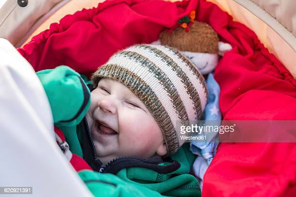 Portrait of laughing baby boy wearing woolly hat