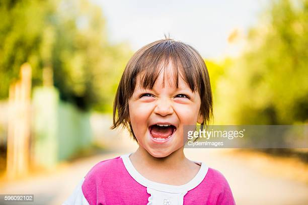 Portrait of laughing baby girl looking away with content smile